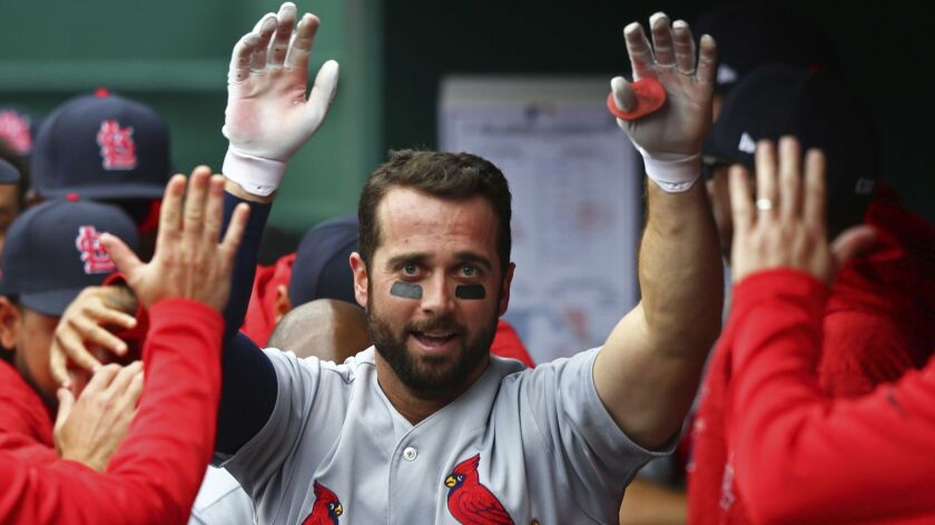 The Cardinals' Greg Garcia high fives teammates after hitting a home run in the fourth inning of a baseball game against the Cincinnati Reds, Saturday, April 14, 2018, in Cincinnati. The Cardinals won 6-1.