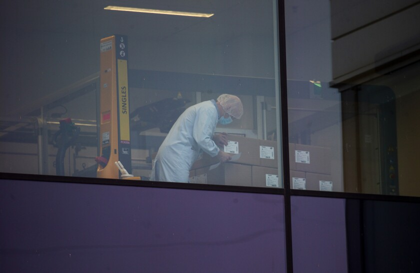 An employee, wearing a protective face mask, checks boxes at a Pfizer manufacturing plant.