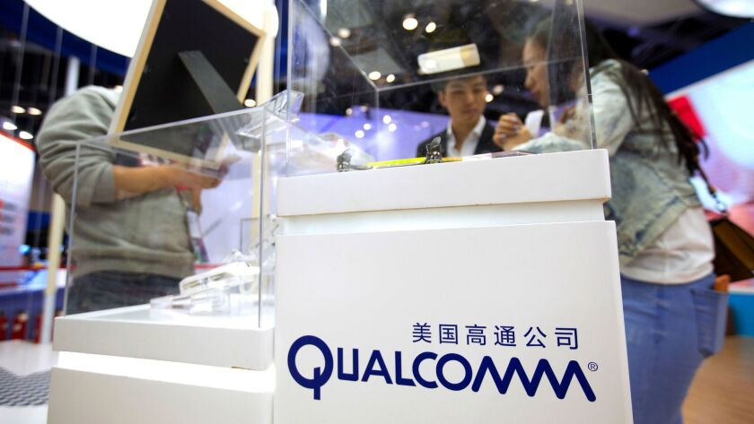FILE - In this Thursday, April 27, 2017, file photo, visitors look at a display booth for Qualcomm a