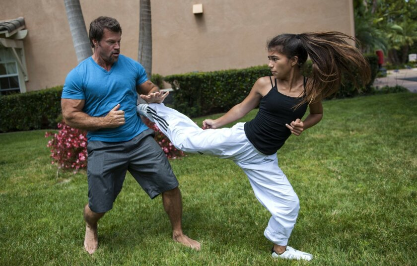 Rayna Vallandingham spars with her dad Jeff on June 26, 2015 in her backyard in Encinitas, CA. When Rayna is not with her coach training at the gym, she practices with her dad at home. .