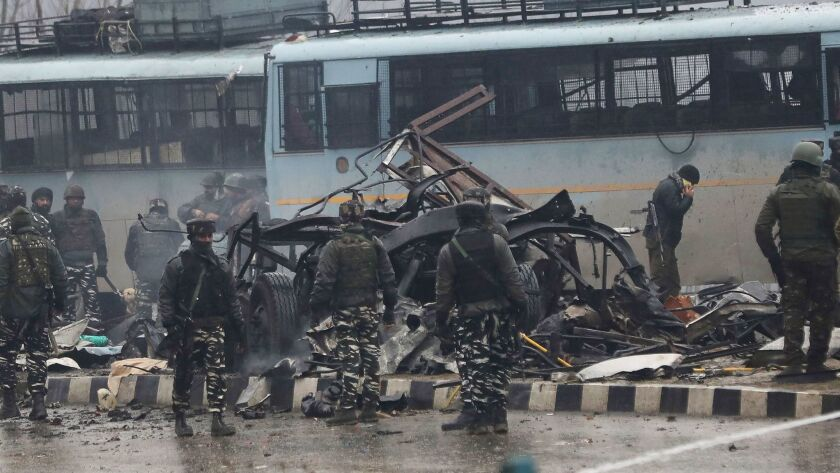 Indian security forces inspect the wreckage of a bus following an attack on a paramilitary Central Reserve Police Force convoy near Awantipora town in Kashmir on Thursday.