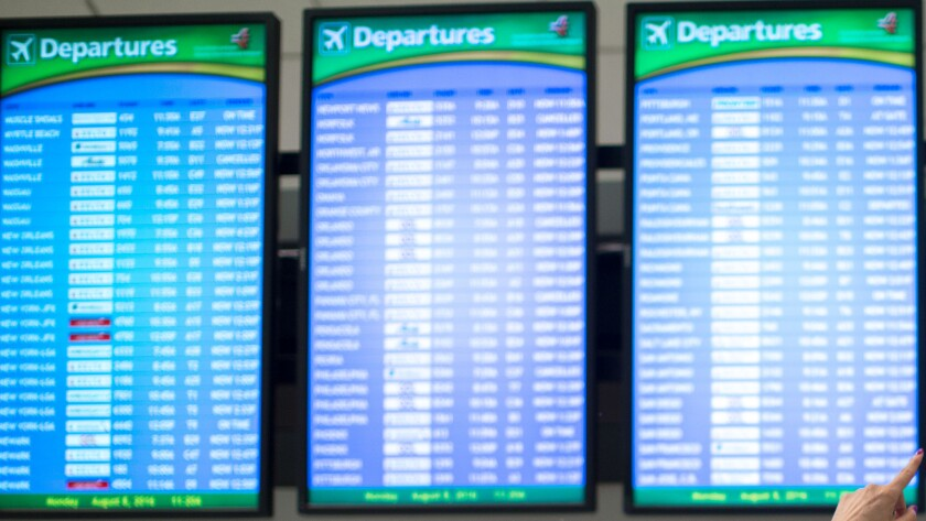 Travelers monitor boards at Hartsfield–Jackson Atlanta International Airport on Monday. Delta Air Lines delayed or canceled hundreds of flights Monday after its computer systems crashed, stranding thousands.
