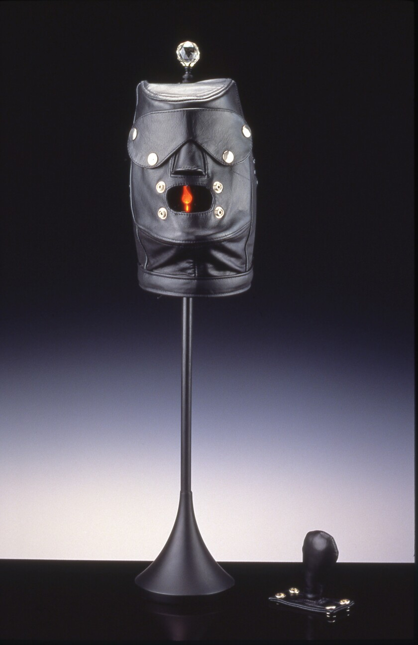 "John Boskovich, ""Ungagged: Scary Hairdresser Coked-Up Table Lamp,"" 1998. Leather bondage mask, metal and electrical lamp fittings, crystal finial, wood base, 28.75 inches by 8.5 inches by  6.5 inches."