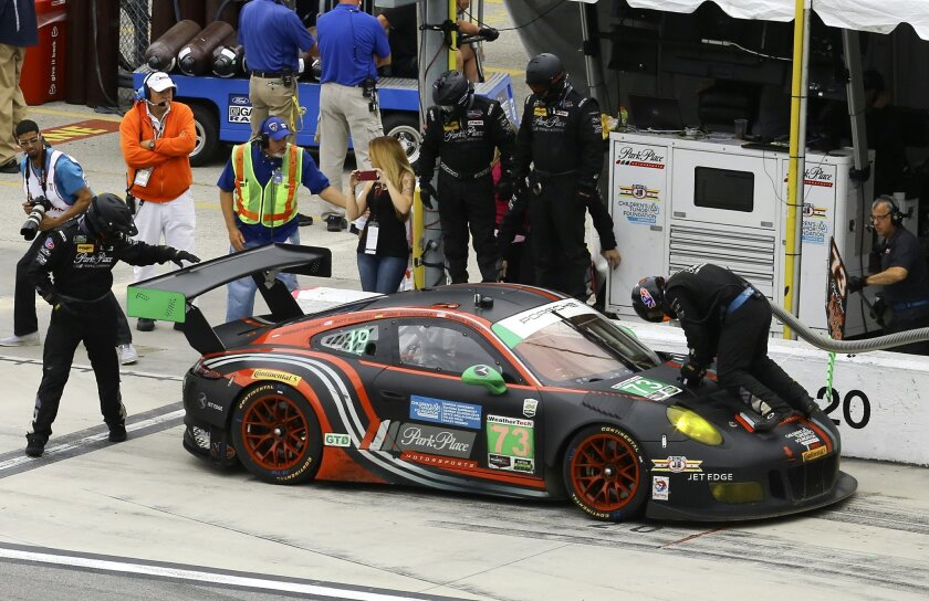 Patrick Lindsey brings the Porsche GT3R (73) in for a pit stop during the final hour of the IMSA 24-hour auto race at Daytona International Speedway, Sunday, Jan. 31, 2016, in Daytona Beach, Fla. (AP Photo/David Graham)