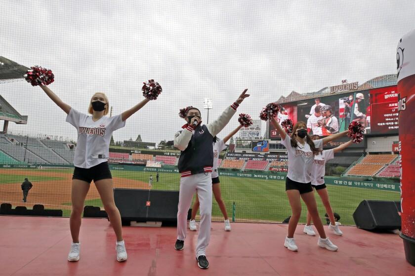 En foto de archivo del 5 de mayo del 2020 porristas del SK Wyverns en un encuentro ante el Hanwha Eagles en Incheon, Corea del Sur. El martes 30 de junio del 2020 portar mascarillas, un lugar vacío entre personas, tomas de temperatura son algunas de las medidas que impondrá la Organización de Béisbol de Corea del Sur para que regresen los aficionados a los estadios en la Liga profesional..(AP Photo/Lee Jin-man, File)