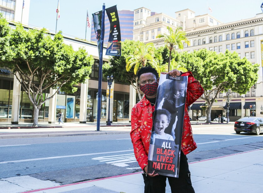 San Diego artist Anthony Tyson holds one of the banners he designed to showcase support for the Black Lives Matter movement