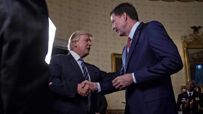 President Trump shakes hands with then-FBI Director James Comey at the White House on Jan. 22, 2017. Trump fired Comey on May 9.