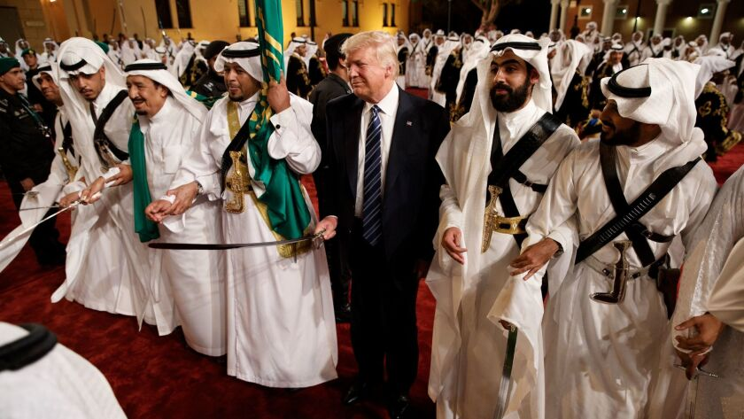 President Donald Trump holds a sword and sways with traditional dancers during a welcome ceremony at