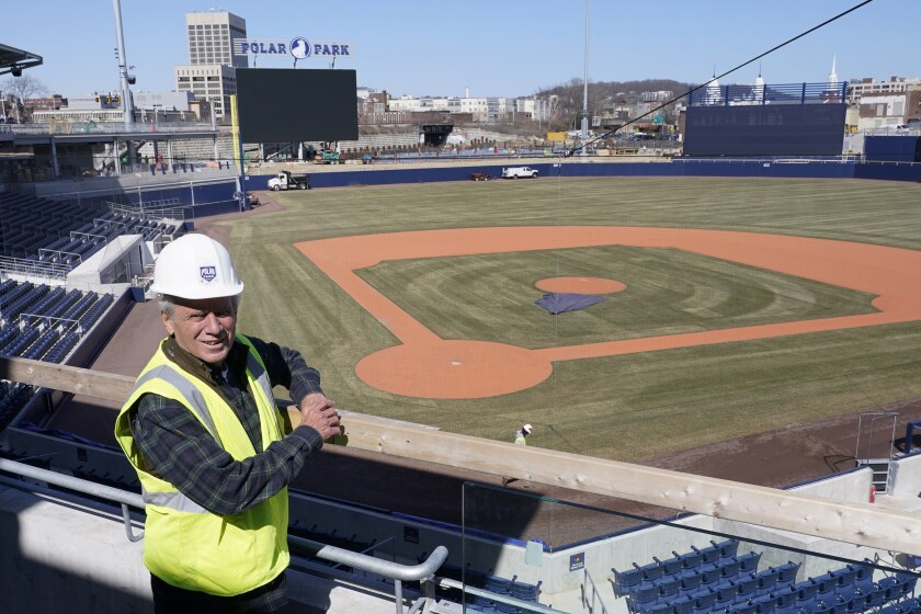 """In this March 22, 2021, photo, Larry Lucchino, Chairman and Principal Owner of the Worcester Red Sox Triple-A baseball team, poses at Polar Park in Worcester, Mass., where construction work continues in preparation for the club's opening day in May. At an age when many ease into retirement, the 75-year-old three-time cancer survivor instead headed to the minor leagues for one more chance to run a baseball team and build it a new home. """"I don't think (retirement) is the way I'm wired,"""" Lucchino said this spring during an interview in the upper deck at the $118 million Polar Park. """"I want to keep doing and being and making and contributing."""" (AP Photo/Elise Amendola)"""