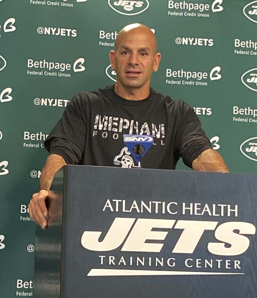 New York Jets coach Robert Saleh speaks to reporters at the team's facility in Florham Park, N.J., on Friday, Sept. 24, 2021, wearing a Mepham High School T-shirt. Saleh wore the shirt to recognize Mepham wide receiver Sofia LaSpina, who was the first female to score a touchdown in Long Island varsity football history. (AP Photo/Dennis Waszak Jr.)
