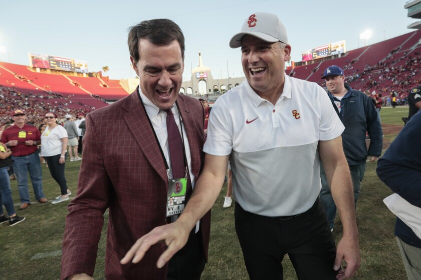 USC athletic director Mike Bohn, left, congratulates USC coach Clay Helton after the Trojans' victory over UCLA in November.