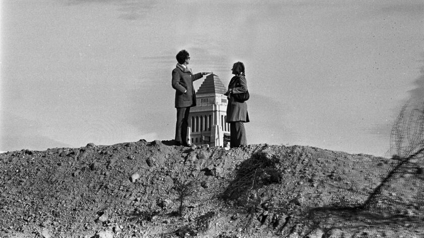 Hugh and Kim Grace stand atop a barren Bunker Hill in 1973 and pretend to touch the top of City Hall in the distance.