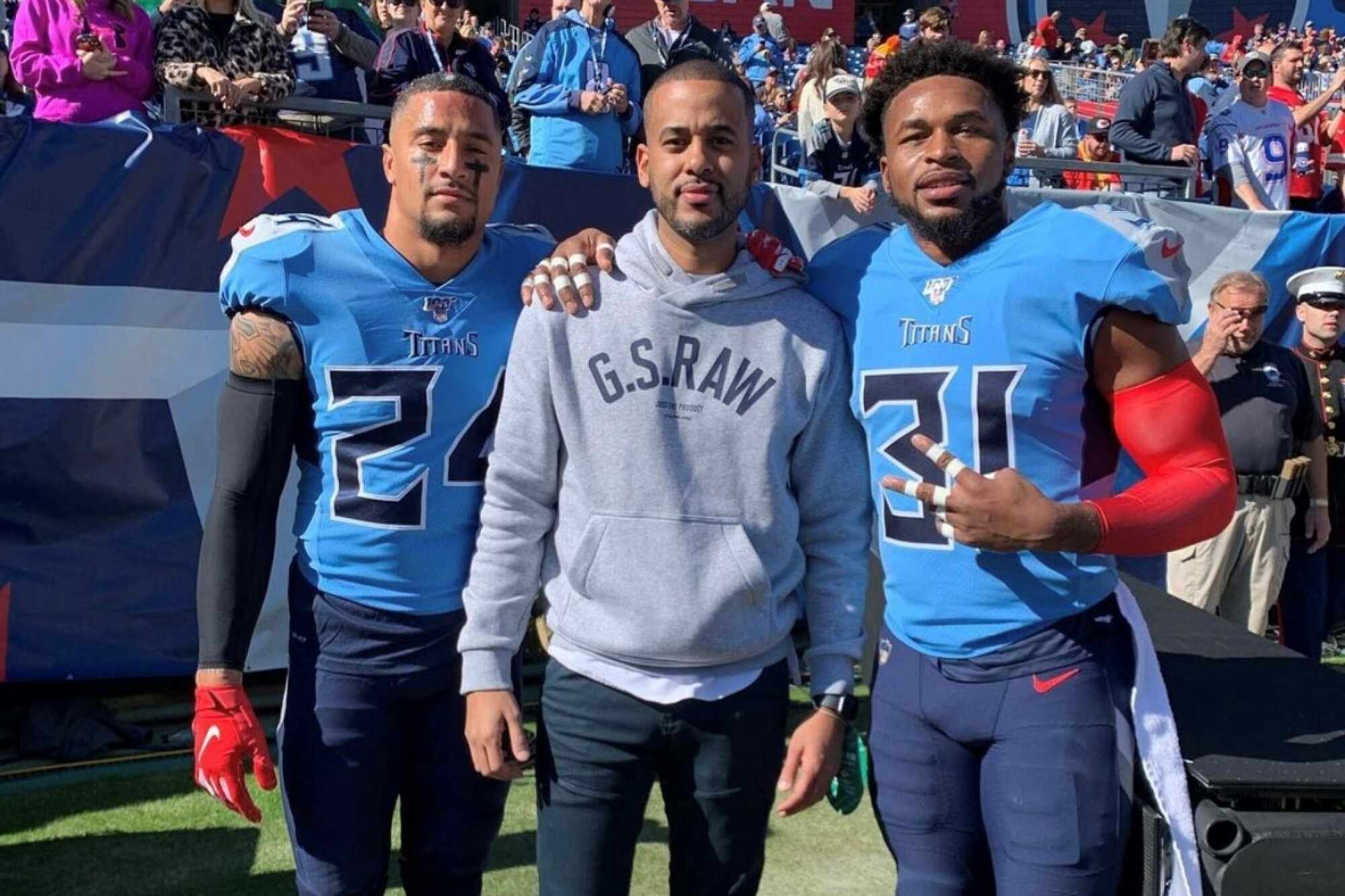 David Mulugheta is flanked by Titans players Kenny Vaccaro, left, and Kevin Byard. .