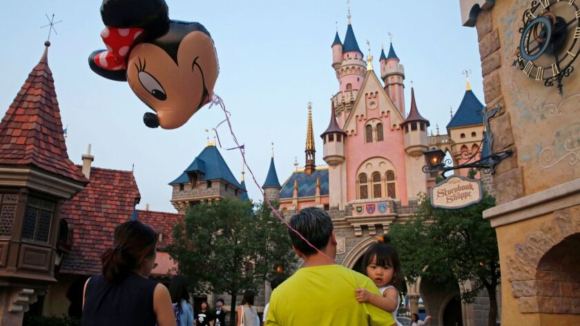 A girl holds a balloon featuring Minnie Mouse at Hong Kong Disneyland. The theme park posted wider annual losses as attendance by mainland Chinese tourists dropped amid a softer tourism market.