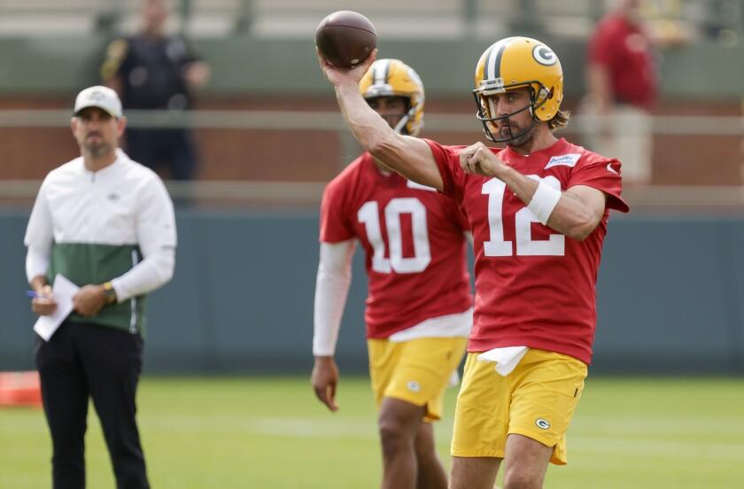 Green Bay Packers' quarterback Aaron Rodgers (12) passes while head coach Matt LaFleur and quarterback Jordan Love (10) watch during NFL football training camp Wednesday, July 28, 2021, in Green Bay, Wis. (AP Photo/Matt Ludtke)