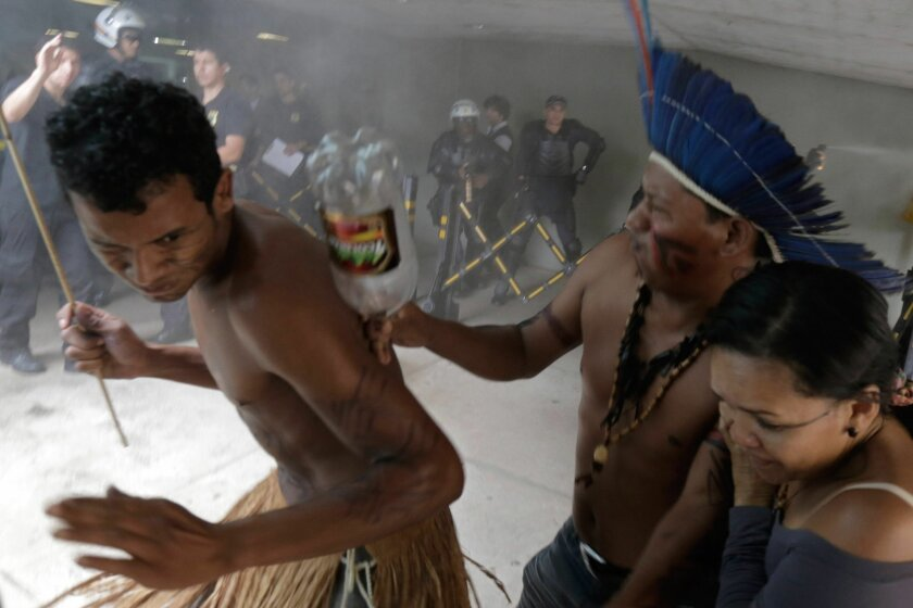 Indians from various tribes run from tear gas fired by police after they tried to enter the Chamber of Deputies where lawmakers are debating the authority to demarcate indigenous lands at Congress in Brasilia, Brazil, Tuesday, Dec. 16, 2014. Brazil's indigenous don't agree with a proposed constitut