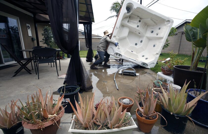 """FILE - This May 6, 2015 file photo a worker empties a spa before removing it at a residence in which the owner considered it """"a waste of water,"""" in Garden Grove, Calif. Purchases totaling about 14,000 acres by Saudi Arabia's largest dairy company have rekindled debate over whether a patchwork of laws and court rulings in the West favors farmers too heavily, especially those who grow thirsty, low-profit crops such as alfalfa at a time when cities are urging people to take shorter showers, skip car washes and tear out grass lawns. (AP Photo/Damian Dovarganes,File)"""