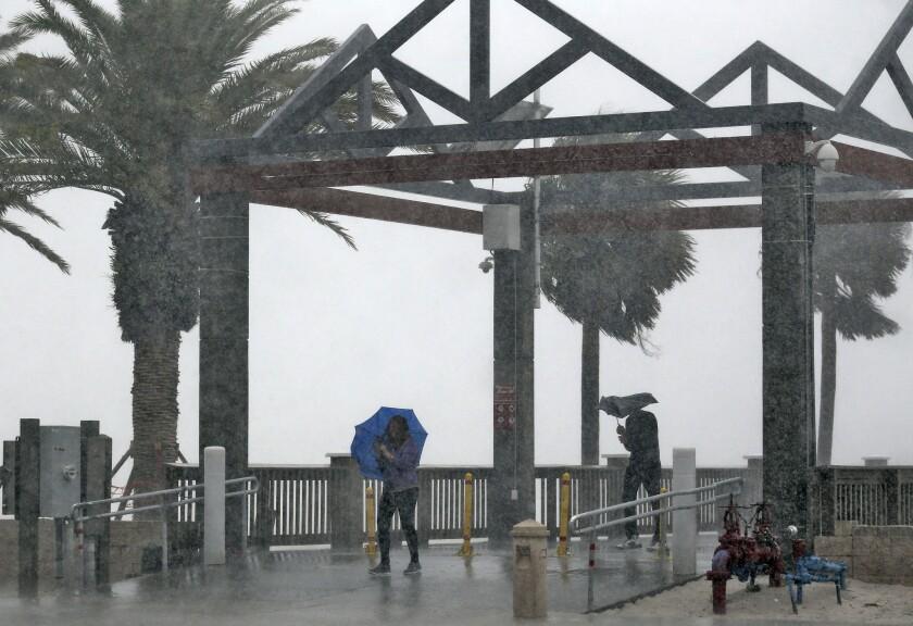 Personas son sorprendidas por un súbito aguacero relacionado con la tormenta tropical Colin en Clearwater Beach, en Clearwater, Florida, el lunes 6 de junio de 2016. Una gran porción del oeste y el noroeste de Florida se encontraba en alerta de tormenta tropical cuando el Centro Nacional de Huracanes anunció que una depresión de desplazamiento veloz se había convertido en una tormenta con nombre. (AP Foto/Chris O'Meara)