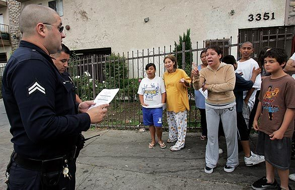 Drew Street resident Patricia Gomez scolds police officers because her children were frightened by the early morning raid on her building targeting reputed gang members. The Avenues gang's Drew Street clique has kept control over the neighborhood despite a series of efforts by federal and local law enforcement agencies over the years, officials said.