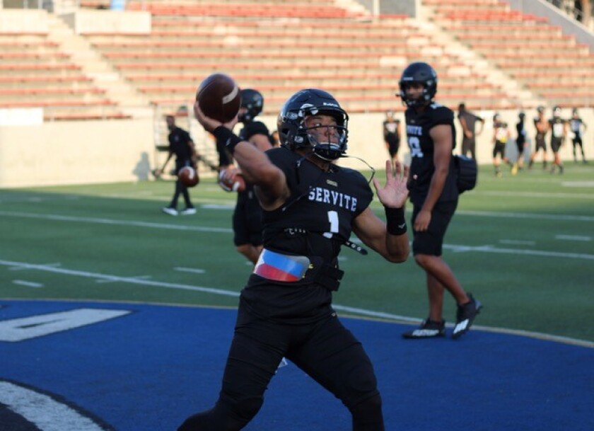 Servite quarterback Noah Fifita warms up before a game against Edison.