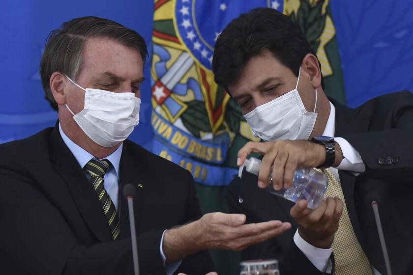 Brazil's Health Minister Luiz Henrique Mandetta, right, gives antibacterial gel to President Jair Bolsonaro