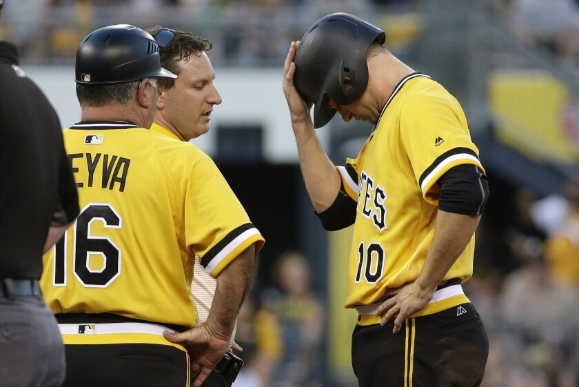 Pittsburgh Pirates' Jordy Mercer (10) holds as his head after being injured sliding into second base in the first inning of a baseball game against the Los Angeles Dodgers in Pittsburgh, Sunday, June 26, 2016. Mercer left the game. (AP Photo/Gene J. Puskar)