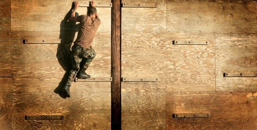 A Navy SEAL candidate climbed a wall as part of the obstacle course at the Naval Special Warfare center in Coronado.