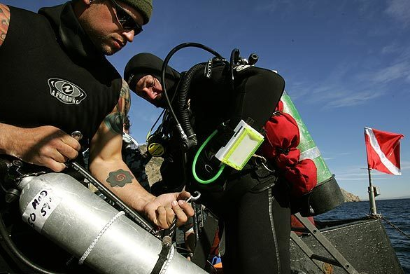Donny Neal attaches a special dive tank to a harness worn by Paul Tattreau. The tank held a special nitrous oxide mixture that enabled them to spend more time at the bottom while reducing the chances of getting sick.