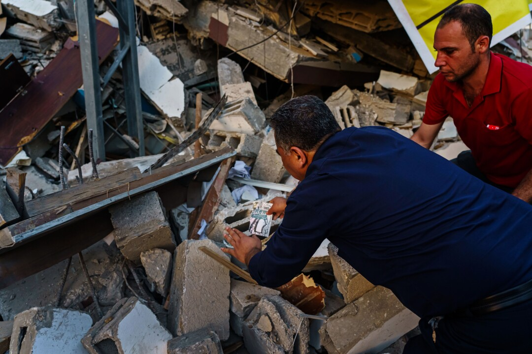 Samir Mansour collects books on the rubble