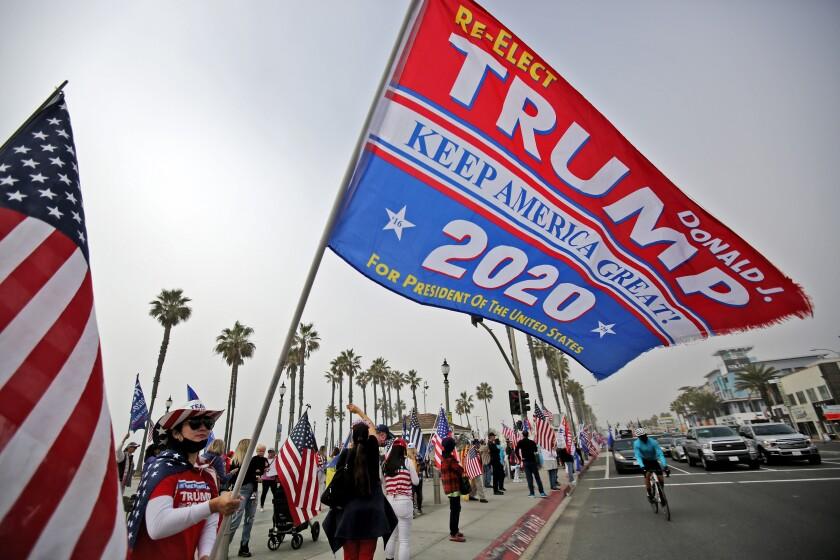 Vu Son waves a Trump election flag during an election rally at Huntington Beach Pier on Wednesday.