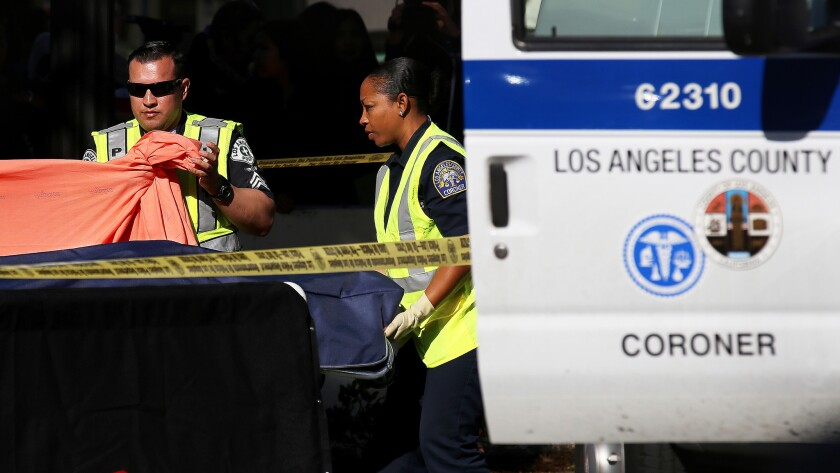 A person from the Los Angeles County Coroner's office removes the body of a student who was killed in a vehicle versus pedestrian accident on Tuesday, Dec. 15, 2015.