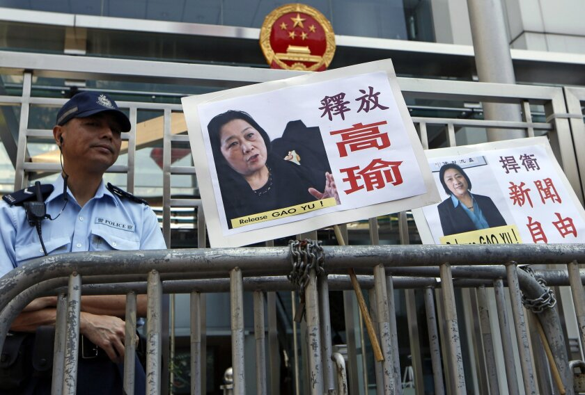 Signs with images of jailed veteran Chinese journalist Gao Yu placed by protesters outside tje Chinese government's liaison office in Hong Kong on Friday.