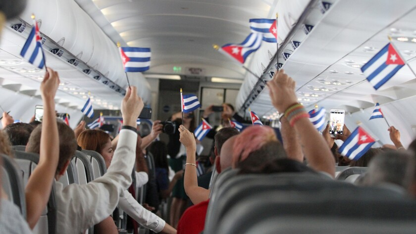 Passengers wave Cuban flags during JetBlue's inaugural commercial flight to Cuba on Wednesday.