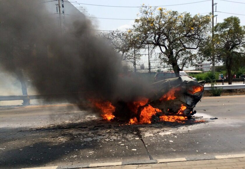 A Ford Fiesta burns after it was slammed into by a black Mercedes killing it's two occupants on a Thai highway on March 13, 2016. The smaller car burst into flames and the couple inside, both graduate students in their 30s, died at the scene of the accident. (Senior Sergeant Major Parichart Pangrith via AP)