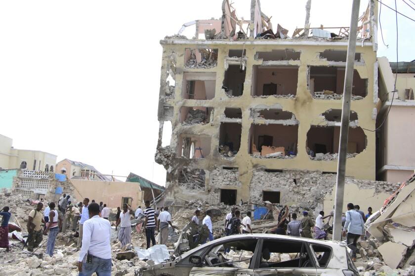 Somalis crowd at a hotel heavily damaged by a car bomb blast in Mogadishu, Somalia, Wednesday, Jan 25, 2017.