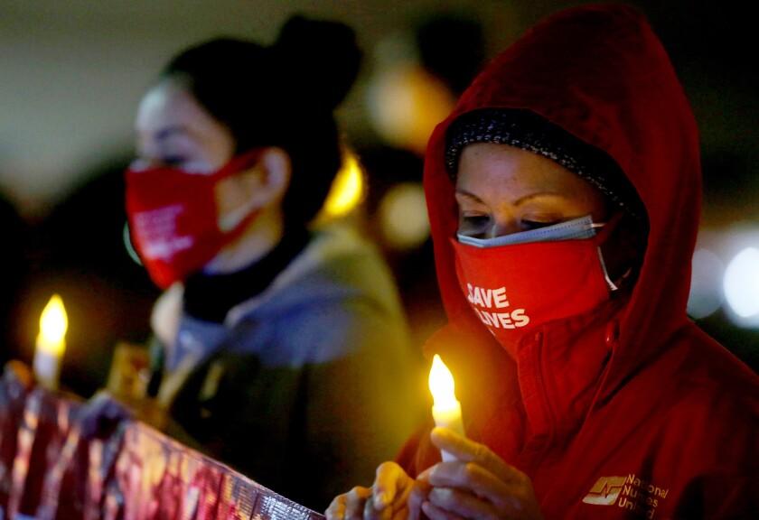 Registered nurses in masks hold a candlelight vigil.