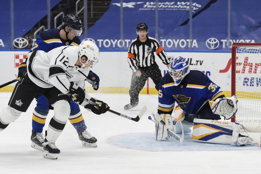 St. Louis Blues' Torey Krug (47) and St. Louis Blues' Ville Husso (35) defends the net against Los Angeles Kings' Trevor Moore (12) during the second period of an NHL hockey game Sunday, Jan. 24, 2021, in St. Louis. (AP Photo/Joe Puetz)