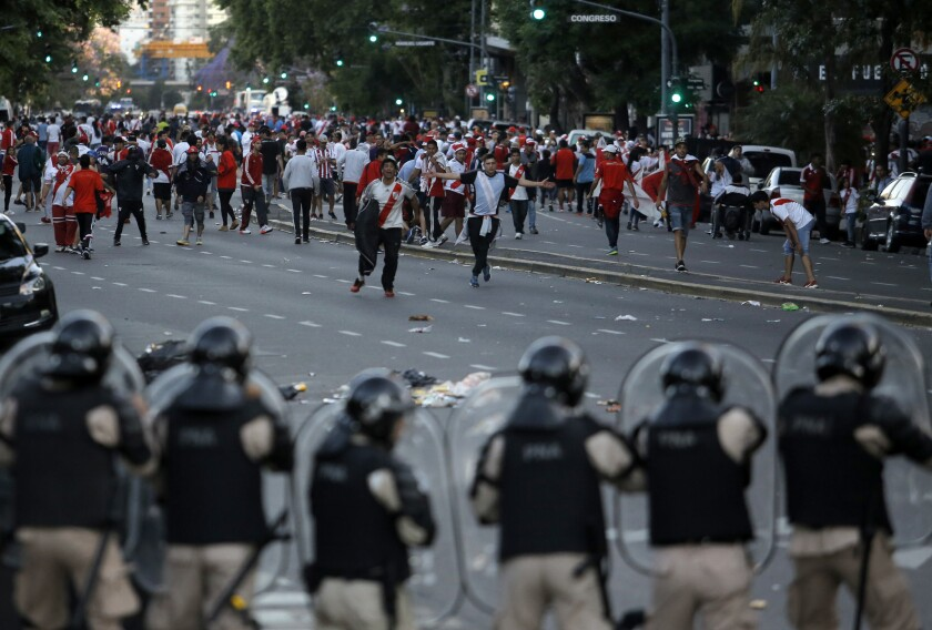 In this Saturday, Nov. 24, 2018 photo, Argentina River Plate fans clash with riot police outside the Antonio Vespucio Liberti stadium prior the final soccer match of the Copa Libertadores between River Plate and Boca Juniors, in Buenos Aires, Argentina. The match has been rescheduled after the bus carrying the Boca Juniors players was attacked by River Plate fans, injuring several players. The match will be played on Sunday.