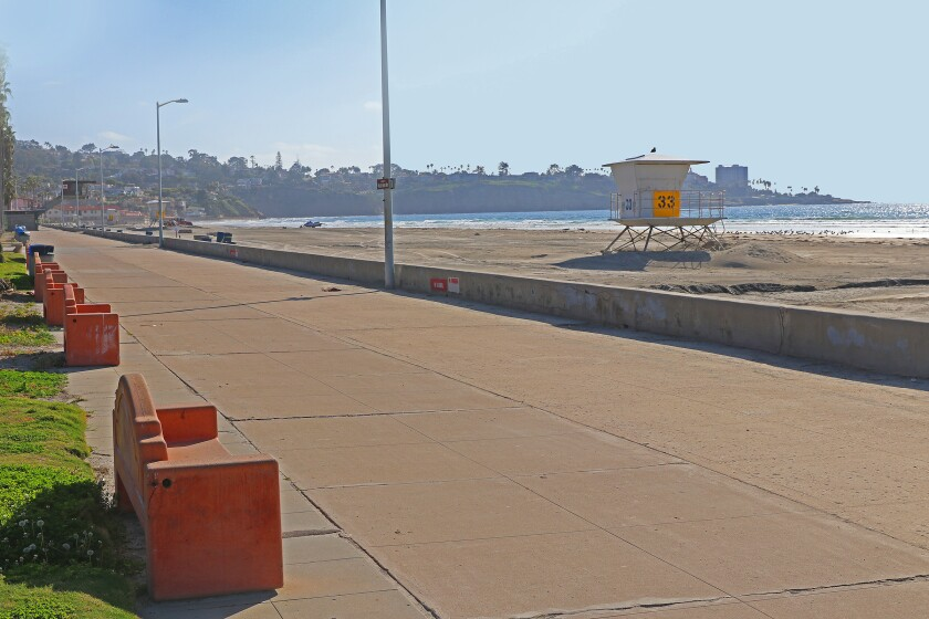 EERILY EMPTY — La Jolla Shores would normally be filled with beacher-goers on a sunny, spring afternoon as photographed Saturday, April 4, 2020; but emergency regulations by both the City and County of San Diego have closed beaches, banned going into the ocean and prohibited public gatherings to help stop the spread of coronavirus (COVID-19). The perimeter of La Jolla Shores Beach is closed off with posted closure notices, yellow caution tape, traffic cones and also watched by police officers stationed nearby. Since the end of March, police patrols and ticketed enforcement have increased to stop citizens from stepping foot onto coastal boardwalks, parking lots, grassy areas and and walkways near shutdown parks, beaches and trails in San Diego County. — Reporting by Daniel K. Lew