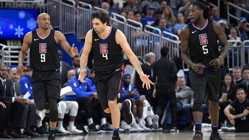 Clippers guard Milos Teodosic (4) celebrates after scoring while jogging up the court with guard C.J. Williams (9) and forward Montrezl Harrell (5) during the second half against the Orlando Magic on Wednesday.