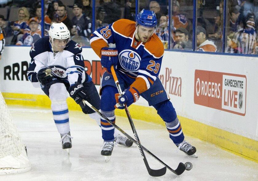 Winnipeg Jets' Tyler Myers (57) chases Edmonton Oilers' Leon Draisaitl (29) during the second period of an NHL hockey game Saturday, Feb. 13, 2016, in Edmonton, Alberta. (Jason Franson/The Canadian Press via AP)