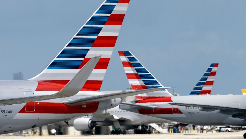 American Airlines planes taxi at Miami International Airport. American plans to add US Airways' planes and pilots to its scheduling system on Saturday, Oct. 1.