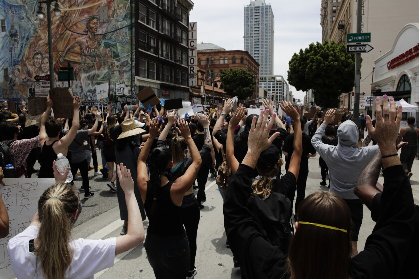 Demonstrators march with their arms raised in Los Angeles, Tuesday, June 2, 2020, in a protest over the death of George Floyd, who died after being restrained by Minneapolis police officers on May 25. (AP Photo/Jae C. Hong)