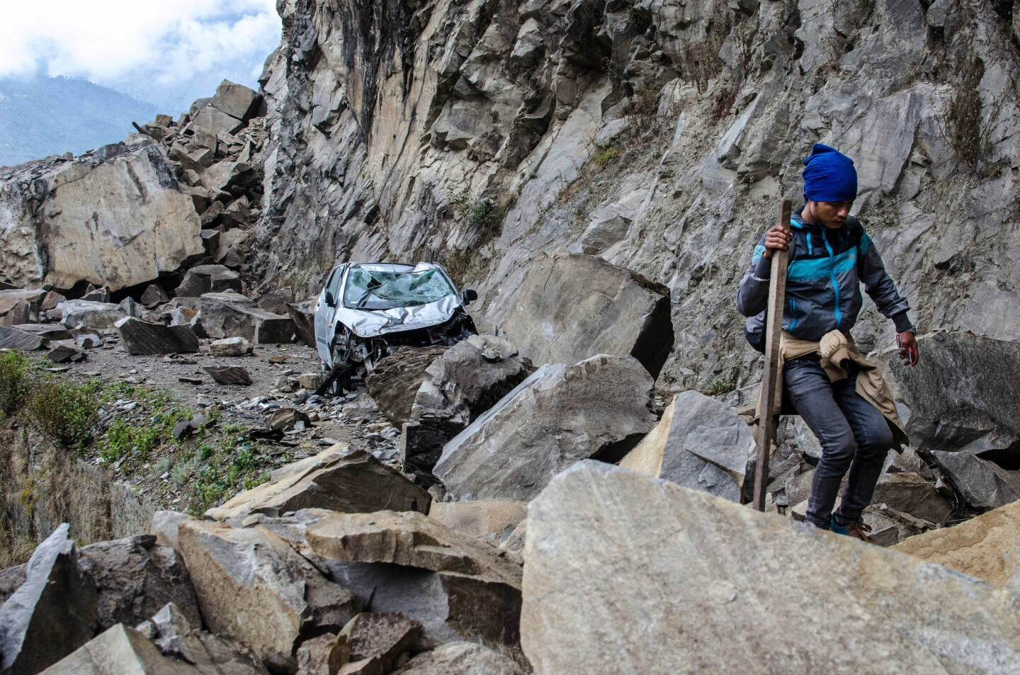 A Nepalese man walks over fallen rocks and past a crushed car on the way to a village in Langtang National Park.