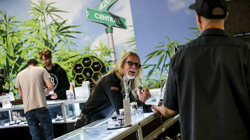 Customer Kurt Elvis, center, talks to 420 Central employee Kevin Gardner, right, on the first day of legal recreational pot sales in California.