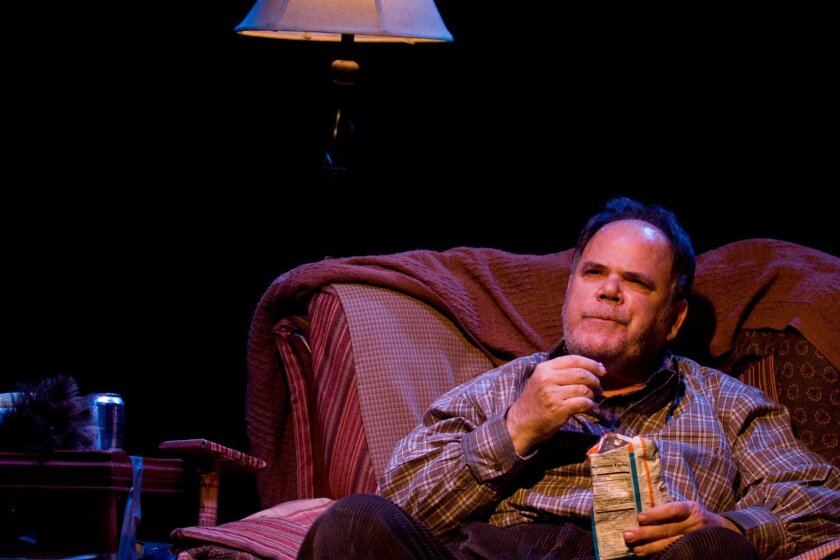 """Mark R. Petrich plays Hetchman, who seemingly is stuck on his couch, in """"A Man, His Wife and His Hat"""" at Moxie Theater. Moxie Theatre photo."""