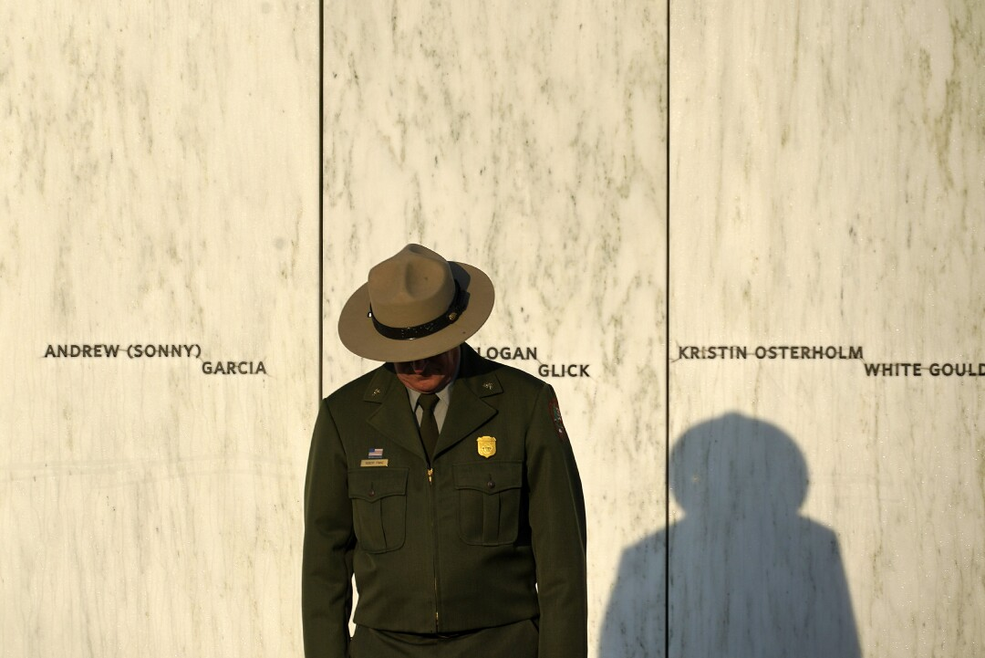 A National Park Service ranger stands in front of the Wall of Names.