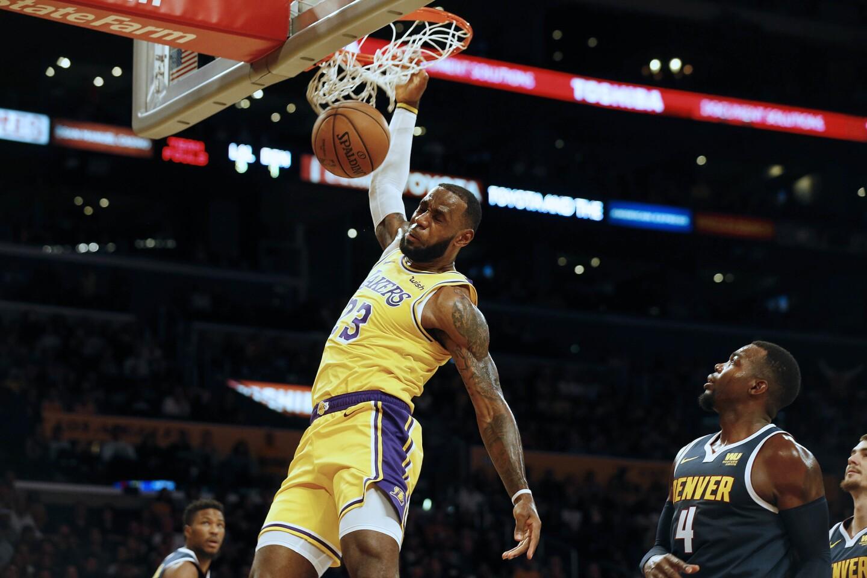 LeBron James dunks ahead of Denver's Paul Millsap.