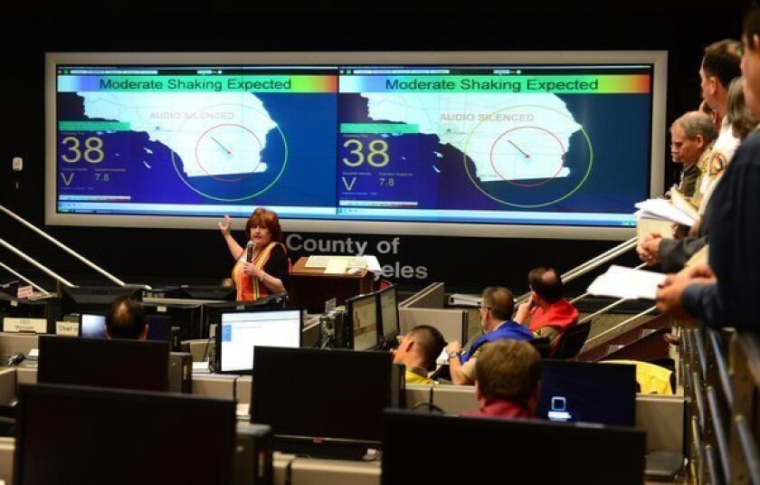 Margaret Vinci from Caltech briefs participants ahead of a functional exercise for first responders in a simulated 7.8 magnitude earthquake drill at the Office of Emergency Management in Los Angeles. This year's exercise featured the California Integrated Seismic Network's Earthquake Early Warning Demonstration System, as seen on screens pictured here.
