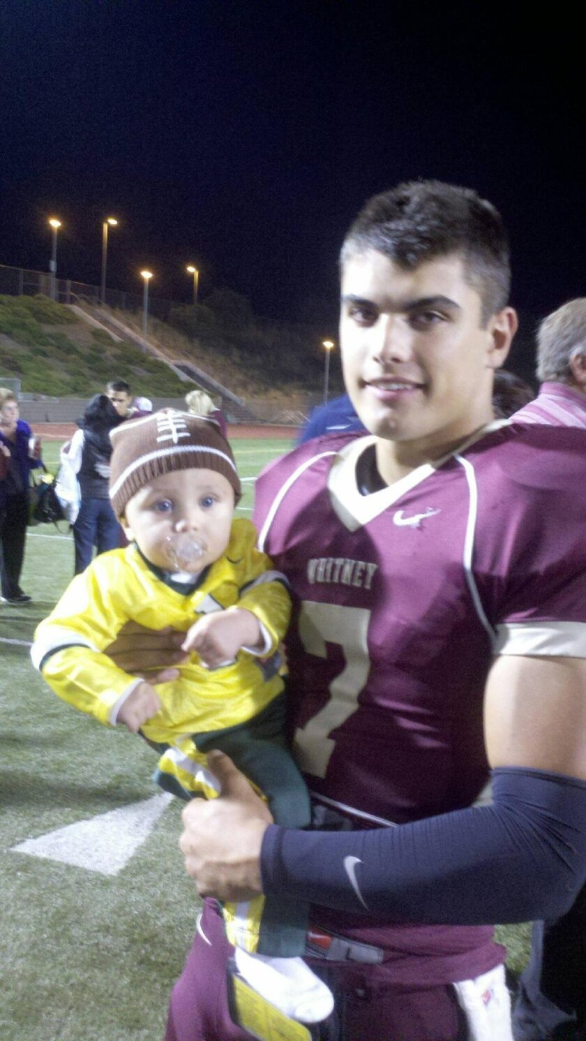 Jake Rodrigues holds his son, Brody, after one of his games at Whitney (Rocklin) High School during his senior year in 2011